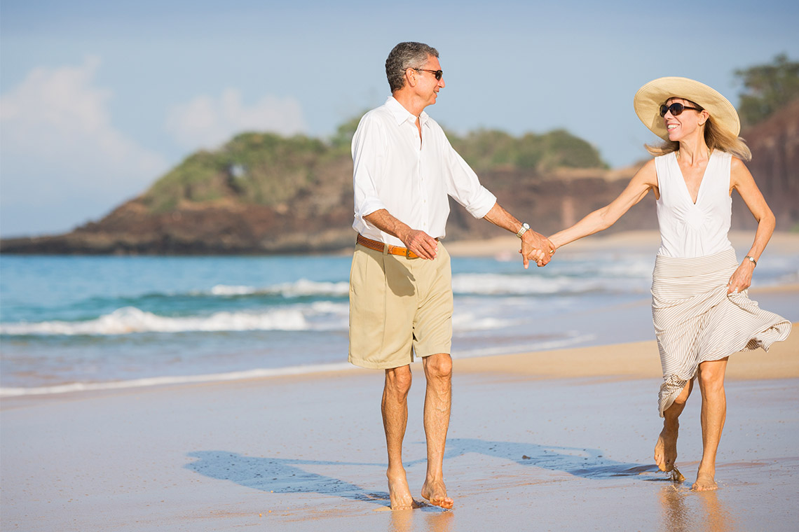 couple with high quality of life walking on beach in Mexico